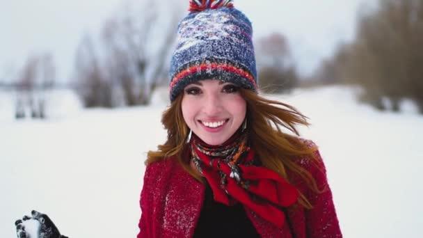 mladá červená hlava žena v červeném kabátě vyvolá sněhová koule zasáhla fotoaparát v super zpomaleně 120fps