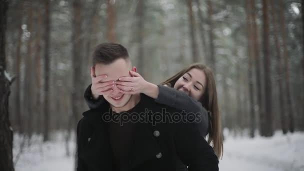 glückliches Paar umarmt und flirtet im Winterwald, lächelt