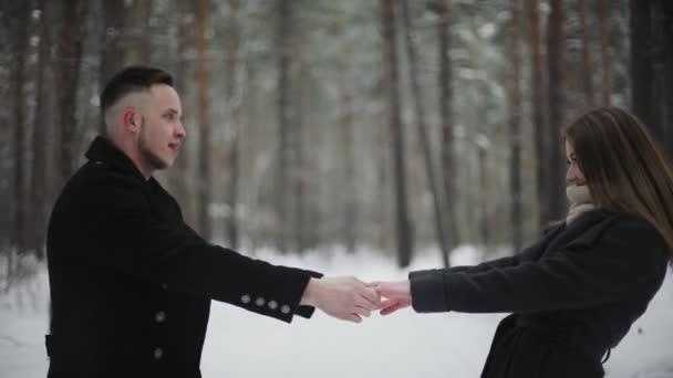 20s člověka je zvedání svou přítelkyni a baví v zimním lese sněhu