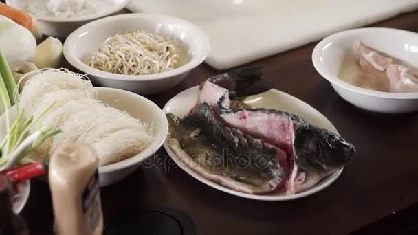 Panoramatický pohled ze zeleniny a ryb na kuchyňský stůl profesionální kuchař