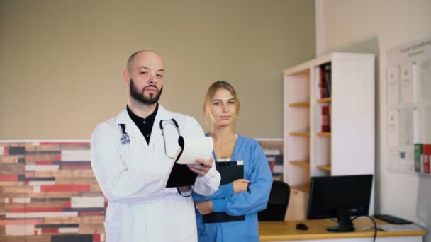 Adult 30s male doctor man with a 20s female nurse in uniform are posing at medical office 4k