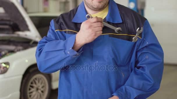 Konzeptporträt eines Automechanikers, der mit einem Schraubenschlüssel die Hände kreuzt