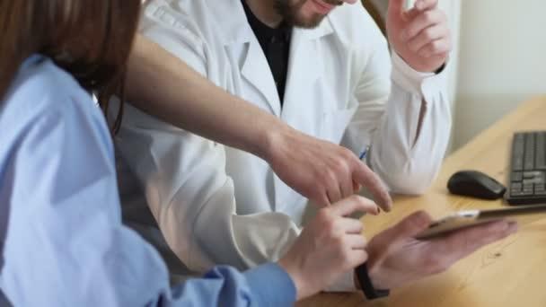 Nahaufnahme eines Tablet-PCs in ein Ärzte-Händen Ärzteteam Arbeit Beratung diskutieren. Sie zeigt mit dem Finger auf dem Touchscreen 4k
