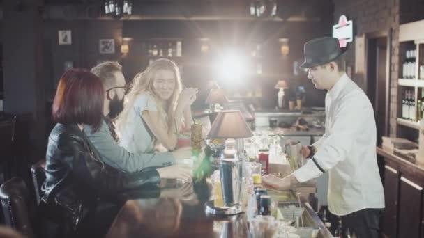 azienda di 20s amici sono dring cocktail mentre barista in cappello sta preparando bevande dietro al bar della festa di notte