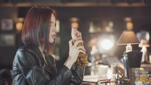20er Jahre sexy Schönheit Rotschopf Frau in schwarzer Lederjacke ist Drink-Cocktail, Blick in die Kamera und Flirt lächelt in der Bar