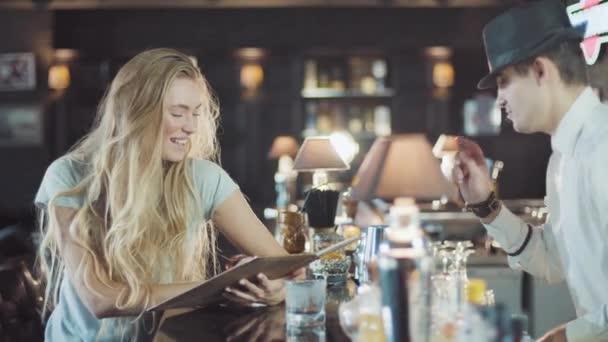 Barkeeper hilft blonder 20er-Jahre-Frau bei der Auswahl in Bar-Menü