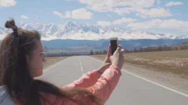 Point of view hands of 20s woman is taking pictures on mobile smart phone with ice peaks and road on backgroung