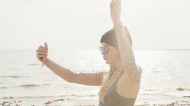 Young blonde with a tattoo in sunglasses and a choker takes off on the phone on the seashore close-up.