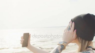 Young blonde with a tattoo on her hand doing selfie on the ocean at sunset time close-up.