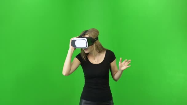 20s blonde woman wearing VR glasses is looking around and concentrated. green chroma key background