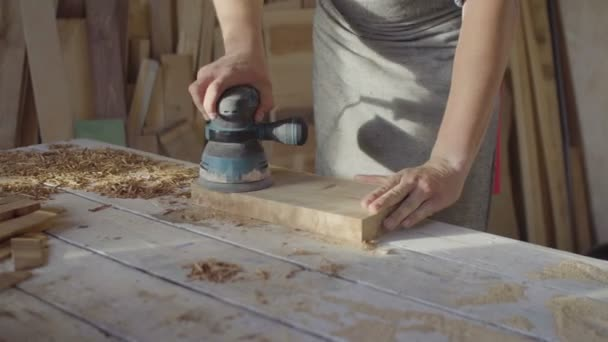 close up hands of carpenter grinding wooden plank on a work table using grind machine