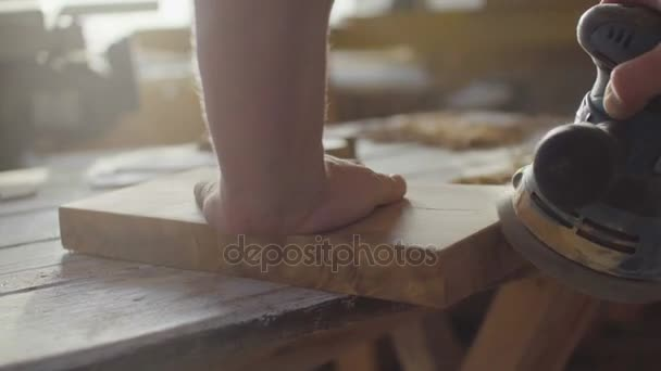Hands of woodworker carpenter grinding wooden plank in backlight using machine
