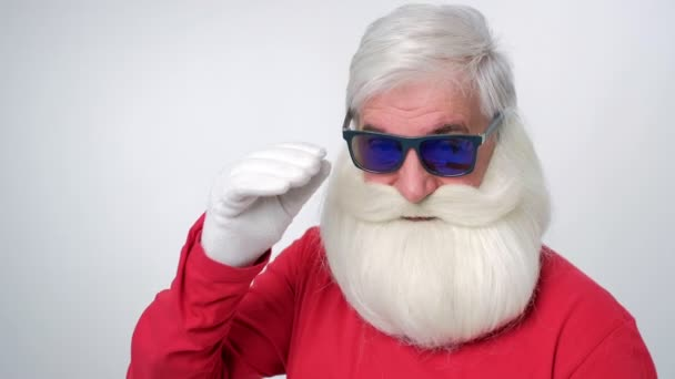 Close up of handsome hipster santa in sunglasses with big white beard looking at camera on a white background