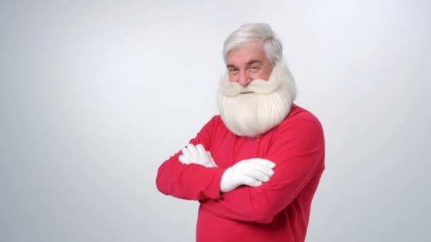 Porträt eines älteren Mannes mit Weihnachtsmütze, der in die Kamera blickt und über hellgrauen Hintergrund zwinkert