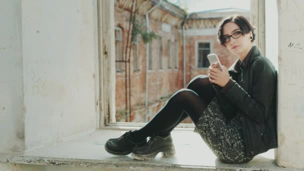 Young hipster woman sitting on a window sill in an old building. Using cell phone