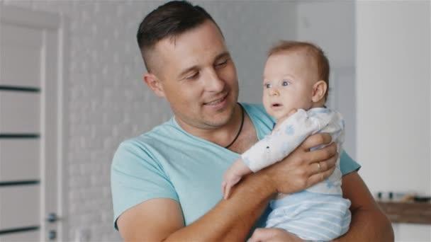 Portrét šťastný otec a syn, dva měsíce v ruce a úsměvem. Radost z otcovství, šťastné dětství