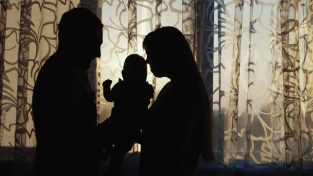 Silhouette of a happy family. Are the house by the window at sunset, gently hold the child in your arms, kiss him