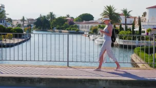 Young tourist woman walking on the bridge over the canal The area