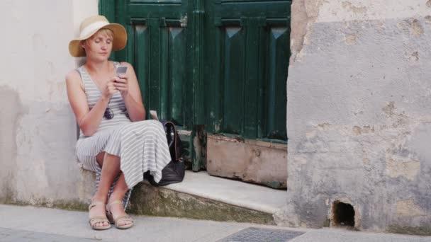 Touristinnen sitzen auf einer Parade alter Haustüren. Handybenutzung