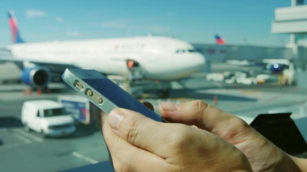 A repülőtéren egy okostelefon segítségével. Háttérben látható a repülőtér és a légi járművek