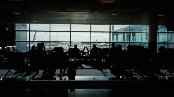 Tracking shot of a large airport terminal. silhouettes of passengers waiting for their flight. Behind the window stand airliners