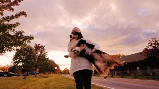 Mladá žena si srandu se svým psem, krouží náručí, se smíchem. Australský ovčák. Zpomalené video
