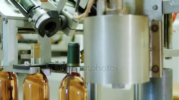Automatické Dopravníkové linky v vinařství. Láhev plná vína se zavře