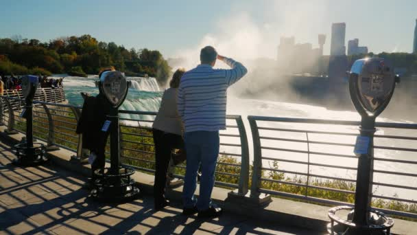 NIAGARA FALLS, NY - OKTOBER 20, 2016: Silhouettes of crowd of tourists admiring the Niagara Falls from the observation deck