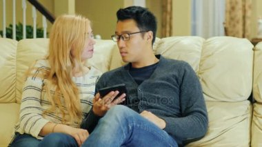 Young multi-ethnic couple spends time at home. enjoy tablet