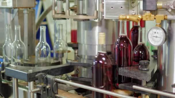 Arbeit im Weingut. Wein wird in Flaschen abgefüllt. dann bewegt und schließt sich auf dem Förderband der Korken