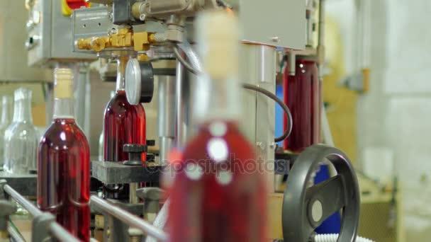 Lahví alkoholu červenou zátkou. Malá hloubka ostrosti