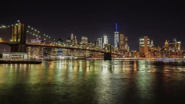 Noční Manhattan a Brooklyn Bridge. Slavný obchodní čtvrti New Yorku. Tok řeky krásně popisuje následující