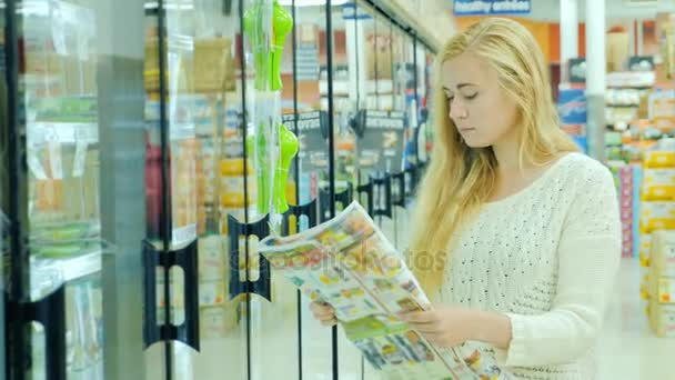 Attractive woman buying food at the supermarket. Read the newspaper with advertising offers. Then take the food out of the refrigerator