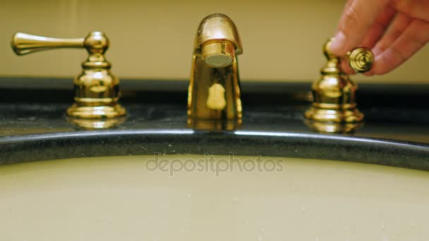 The hand opens the tap water in a vintage washstand