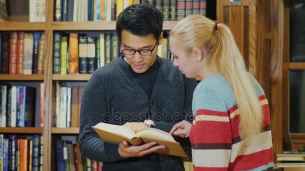 Asijské muž s brýlemi a kavkazské ženy stojící společně sledovat knihu v knihovně. Na pozadí polic s knihami