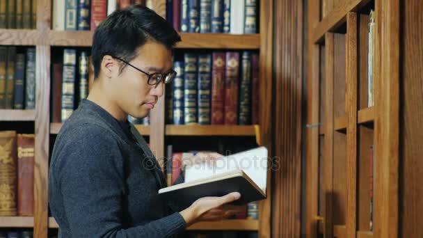 Inteligentní asijské muž hledá knihu v knihovně