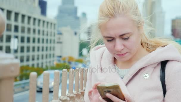 Portrait of a young woman in New York. It should be in the pink coat on a background of Manhattan buildings, typing on smartphone