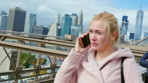 Junge Wome auf das Telefonieren vor dem Hintergrund der Manhattan Wolkenkratzer