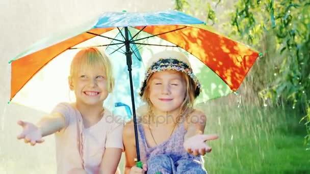 Zwei unbeschwerte Mädchen sitzen unter einem Regenschirm und verstecken sich vor dem warmen Sommerregen. das Konzept - eine glückliche Kindheit
