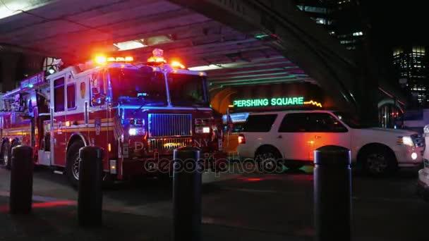 New York, Usa - Okt, 2016: Velké červené hasičské auto s majákem. Stojí na ulici, jděte přes jiné stroje, noční provoz