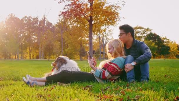 Multietnické Barbora relaxační v parku se svým psem. Kavkazský žena se těší tabletu, korejský muž sedí