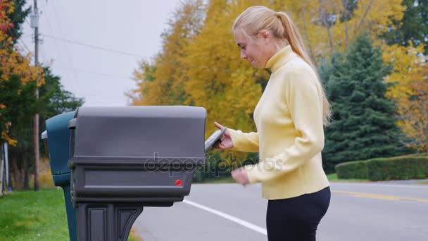 Junge Frau nimmt die Post aus dem Postfach. Landschaft in den Usa