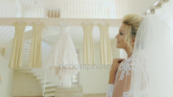 Atraktivní kavkazských nevěsta se dívá na její svatební šaty a šaty družiček. Zadní pohled přes rameno