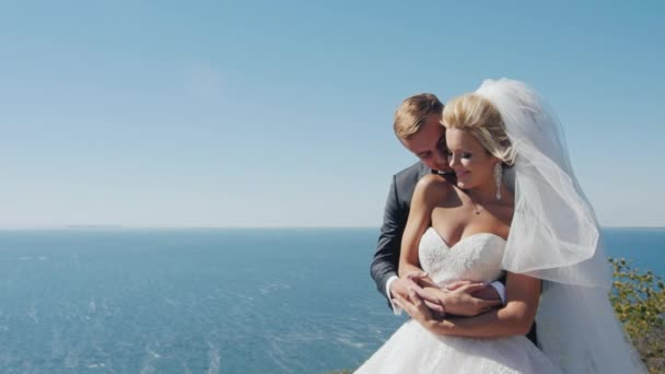 Nevěsta a ženich ve svatebních šatech, stojící na pozadí moře, při pohledu do dálky, objetí