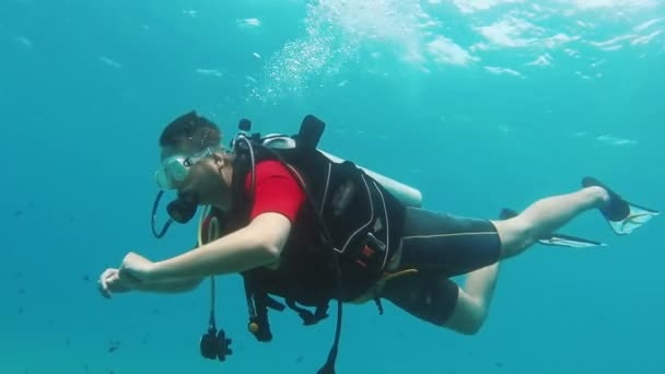 Novice diver learns to swim with scuba diving. Side view