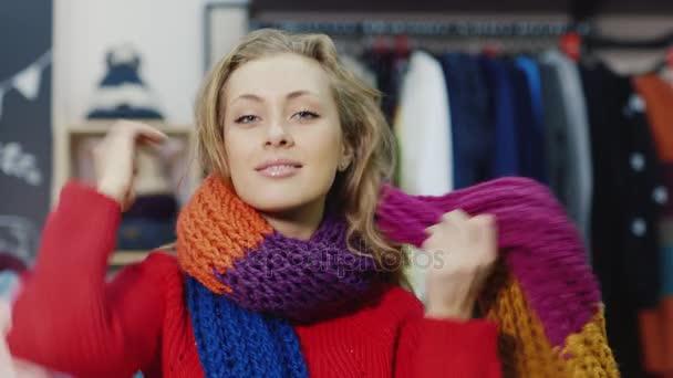 Portrét krásné mladé ženy nosí šátek. Směje se na kameru, stojící v obchodě s oděvy. Úspěšné nakupování