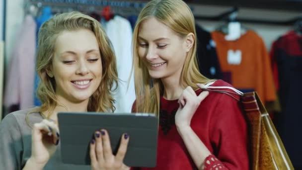 Dvě ženy zákazníci užít tabletu v úložišti. Stojící na pozadí stojany s oblečením: příruční tašky