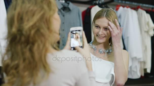 A telefon fényképeztem barátnője. Nő megpróbálja a nyaklánc és ékszer: egy barátom, ő fényképek. sikeres vásárlás