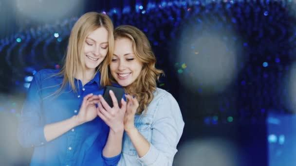 Két fiatal nők meg a telefon használata egy diszkóban, pozitív érzelmek