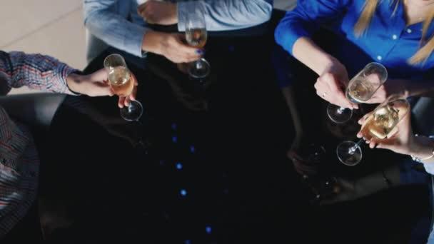 Skupina mladých lidí, pití vína z Připijte si brýle černé zrcadlo stůl. Pohled shora